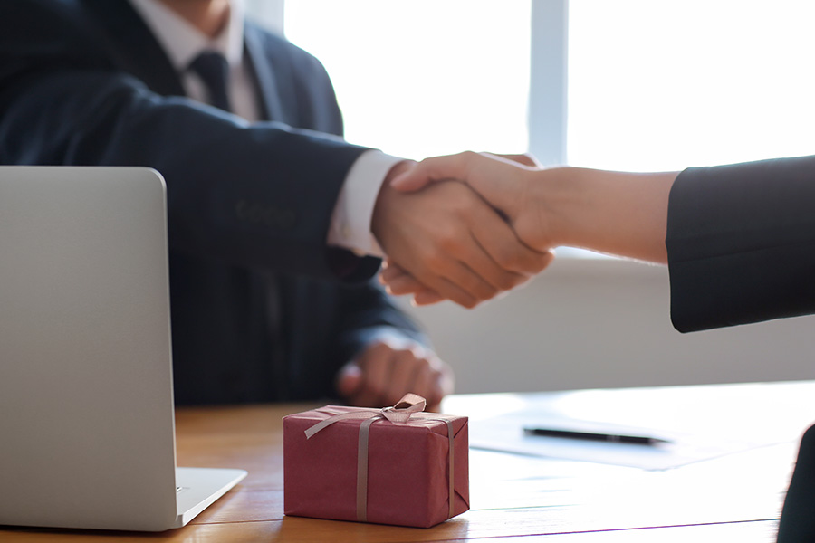 A Gift For You - Business Insurer and Client Shaking Hands After Accepting Small Welcome Gift