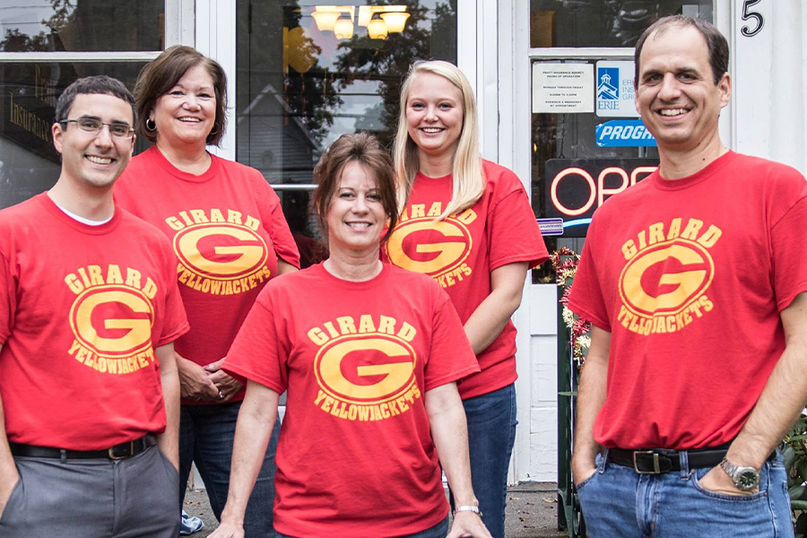 About Our Agency - Team Photo in Matching Red T-shirts in Front of Office Cheering on the Girard Yellowjacket Team