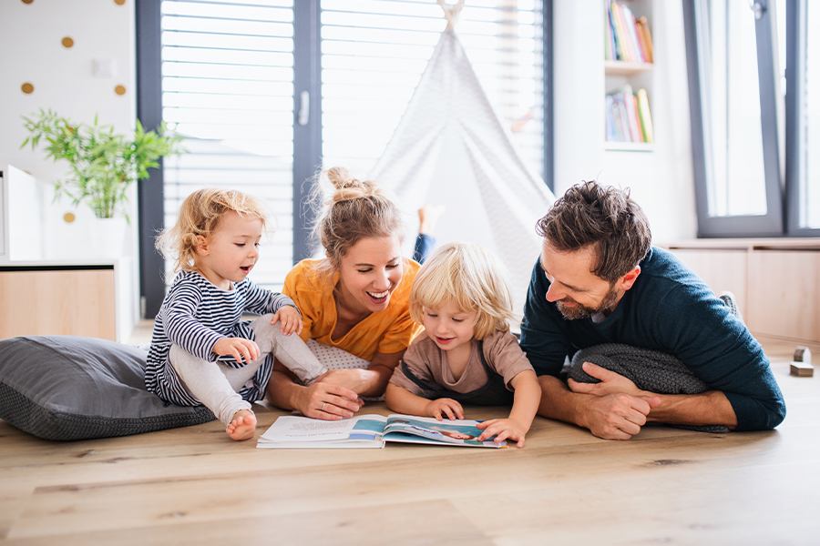 Blog - Young Family with Two Small Children Indoors in the Living Room Reading a Book