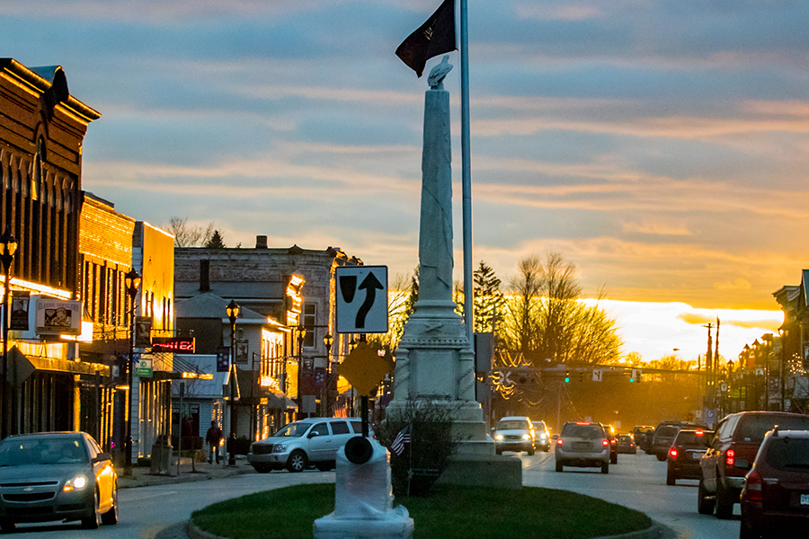Girard, PA - Girard Monument in the Center of Town at Sunset with Cars and Buildings on Either Side at Dusk
